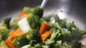 Pan shot of woman cooking vegetable in a pan