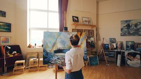 Pan shot of young woman focused on painting seascape on canvas in nice light studio standing near easel alone and. Working. Fine arts and creative people stock video footage