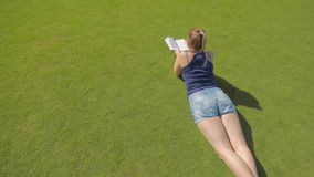 Pan shot of young woman lying on grass and reading a book at sunny day. Pan shot of woman lying on grass and reading a book at sunny day stock video footage