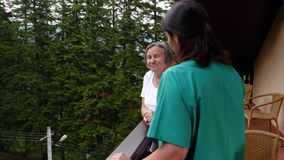Care worker spending time with senior woman in nursing home care center stock video