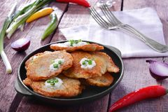 Pan with tasty potato pancakes for Hanukkah. And some ingredients on wooden table Royalty Free Stock Images