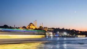 Pan Timelapse-mening van cityscape van Istanboel met Suleymaniye-moskee met toeristenschepen die in Bosphorus bij nacht drijven stock videobeelden