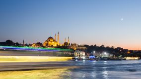 Pan Timelapse view of Istanbul cityscape with Suleymaniye mosque with tourist ships floating at Bosphorus at night stock video footage
