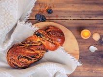 Pan torcido con las semillas de amapola y el huevo del pollo con la yema de huevo y cáscaras quebradas en un fondo del paño ásper Foto de archivo