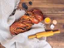 Pan torcido con las semillas de amapola y el huevo del pollo con la yema de huevo y las cáscaras quebradas, rodillo de madera en  Imagenes de archivo