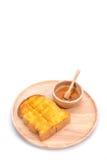 Pan tostado con la miel y cazo de la miel en el fondo blanco Fotos de archivo
