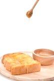 Pan tostado con la miel y cazo de la miel en el fondo blanco Imagenes de archivo
