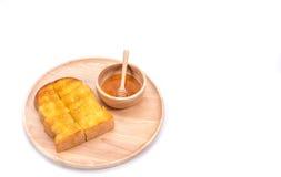 Pan tostado con la miel y cazo de la miel en el fondo blanco Foto de archivo libre de regalías