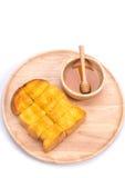 Pan tostado con la miel y cazo de la miel en el fondo blanco Imagen de archivo libre de regalías