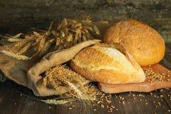 Pan, trigo, espigas de trigo en un fondo de madera Imagen de archivo libre de regalías