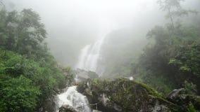 Pan Up de la cascade faisante rage à embrumer pendant la tempête de pluie - Sapa Vietnam banque de vidéos