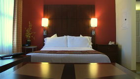 Pan up in Hotel room. A pan up view of a contemporary hotel bed room stock footage