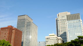 Pan Up of Office Buildings Surrounded by Trees in Central Tokyo Japan stock footage
