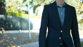 Pan up portrait of young successful businessman walking towards job interview or meeting concept. Young successful businessman in the park going to work concept stock footage