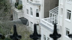 Pan up, pull focus from old victorian iron railings to a London home. stock video