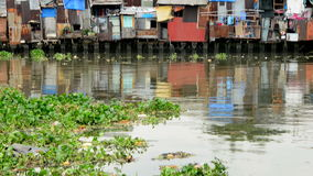 Pan up of Shacks on the Saigon River - Ho Chi Minh City (Saigon) - stock video