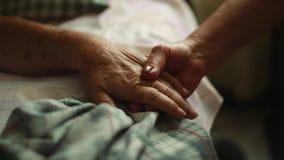 Pan van de Bejaarde handen van de persoonsholding aan het bed waar zij ligt stock videobeelden