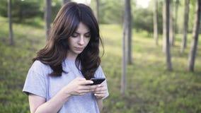 Pan van een jonge vrouw met een smartphone in een park wordt geschoten dat stock video
