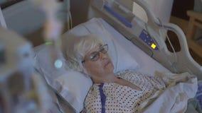 Pan van gedeprimeerd bejaarde in het ziekenhuisbed stock footage