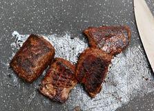Pan-verbranntes Steak auf Schneidebrett Stockbilder