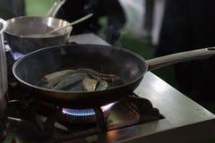 Pan verbrennen Fische auf einer heißen Wanne mit Gasbrennerflamme lizenzfreies stockbild