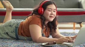 Pan video shot,An Asian fat woman is lying down on the floor and working at home. At the same time, she ate food, being an unhygie