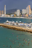 Pan view of Benidorm Poniente beach with port, skyscrapers, boats and mountains in Benidorm, Alicante, Spain with rain clouds on b Stock Images