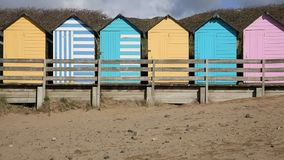 Pan view of numerous colourful English beach huts traditional English structure and shelter found at the seaside stock video footage