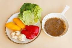 Pan von bagna Cauda mit einem Teller des Gemüses als Zutat Stockfoto