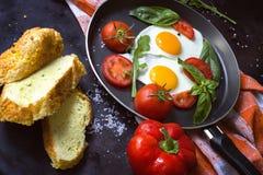 Pan von Spiegeleiern, von Basilikum und von Tomaten mit Brot auf metallischer Tischplatte des Schmutzes Lizenzfreie Stockfotografie