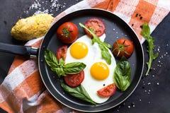 Pan von Spiegeleiern, von Basilikum und von Tomaten mit Brot auf metallischer Tischplatte des Schmutzes Lizenzfreie Stockfotos