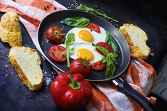 Pan von Spiegeleiern, von Basilikum und von Tomaten mit Brot auf metallischer Tischplatte des Schmutzes Lizenzfreies Stockfoto