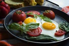 Pan von Spiegeleiern, von Basilikum und von Tomaten mit Brot auf metallischer Tischplatte des Schmutzes Stockfotos