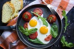 Pan von Spiegeleiern, von Basilikum und von Tomaten mit Brot auf metallischer Tischplatte des Schmutzes Stockbild