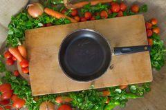 Pan on a wooden board with tomatoes, salad, onion and carrots Royalty Free Stock Images