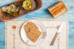 Pan y aceite de oliva deletreados en una tabla de madera Foto de archivo