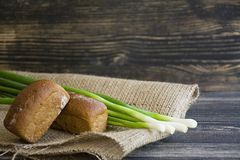 Pan y cebolla verde recientemente cocidos en un fondo de madera oscuro fotografía de archivo
