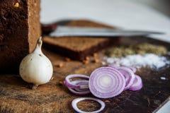 Pan y cebollas en una sal de la tabla de cortar Foto de archivo