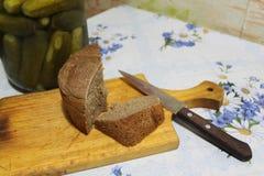 Pan y cuchillo en tabla de cortar Fotografía de archivo