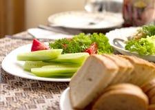 Pan y diversas ensaladas de los tomates, pepinos en las placas blancas en una tabla en un restaurante Foto de archivo
