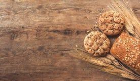 Pan y galletas con trigo en una superficie de madera con el espacio para el texto imágenes de archivo libres de regalías