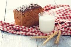 Pan y leche con las espiguillas del trigo en un paño en tableros Fotografía de archivo libre de regalías