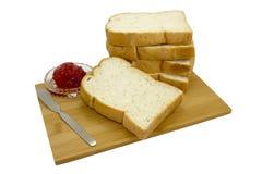 Pan y mermelada de fresa aislados en el tablero de madera Foto de archivo