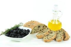 Pan y productos brutos verdes olivas mediterráneos rebanados. Foto de archivo