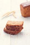 Pan y rebanadas de pan con la espiguilla del trigo en tableros Imagen de archivo