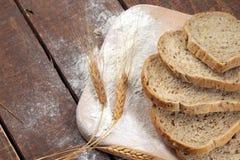 Pan y trigo rústicos en una tabla vieja de madera del vintage Foto de archivo
