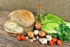 Pan y verduras en la tabla Imagen de archivo libre de regalías
