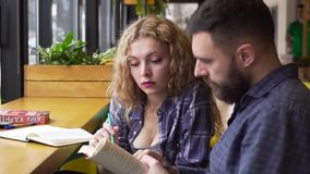 PAN of young woman explains to a young man a complex material in a book sitting in a cafe.  stock video footage