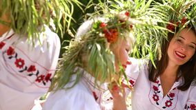Women in ethnic dresses modelling outside. Pan of young women in ethnic dresses and flower circlets smiling at camera outside. Cheerful slavic girls modelling in stock video