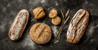Panadería - barras de pan y bollos crujientes rústicos en negro foto de archivo libre de regalías